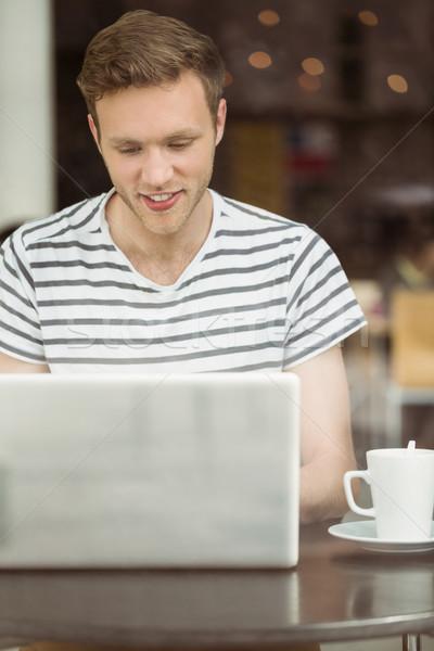 Sorridente estudante sessão bebida quente usando laptop café Foto stock © wavebreak_media