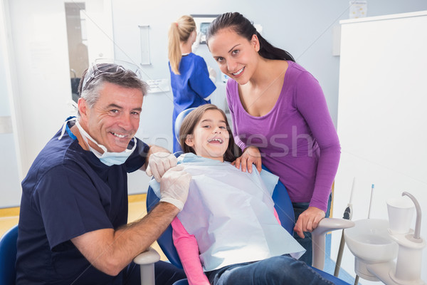 Smiling pediatric dentist with a happy young patient and her mot Stock photo © wavebreak_media