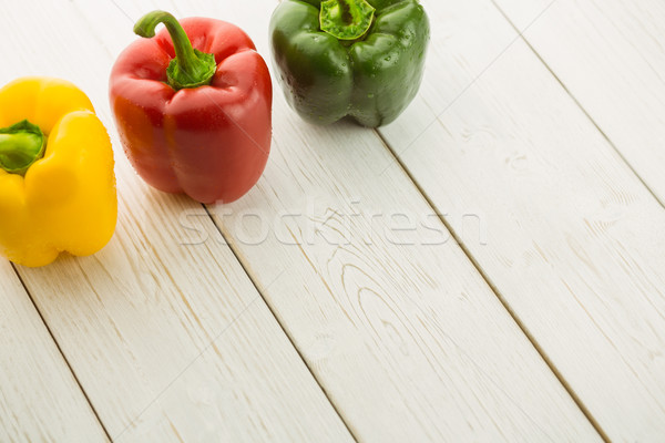 Three peppers on chopping board Stock photo © wavebreak_media