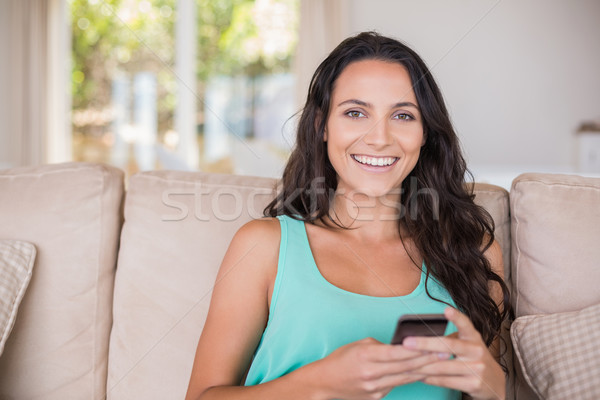 Csinos barna hajú sms chat okostelefon otthon nappali Stock fotó © wavebreak_media