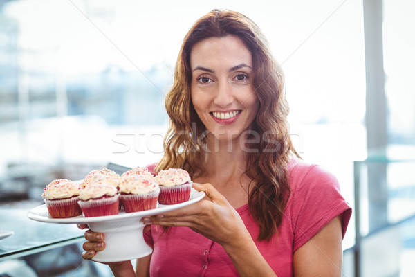 Pretty brunette showing plate of pastries Stock photo © wavebreak_media