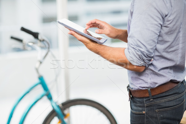 Businessman scrolling on his tablet in the office Stock photo © wavebreak_media