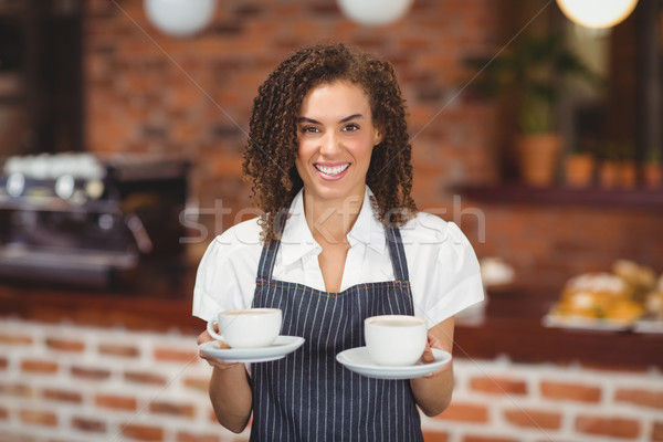 Smiling barista serving two cups of coffee Stock photo © wavebreak_media
