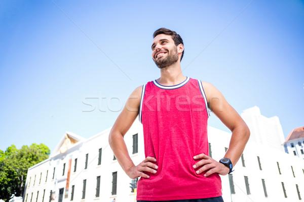 Smiling handsome athlete with hands on hips Stock photo © wavebreak_media