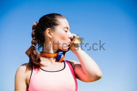 Composite image of portrait of sportswoman kissing her medals  Stock photo © wavebreak_media