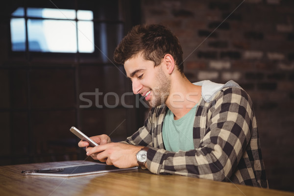 Smiling hipster sitting and texting Stock photo © wavebreak_media