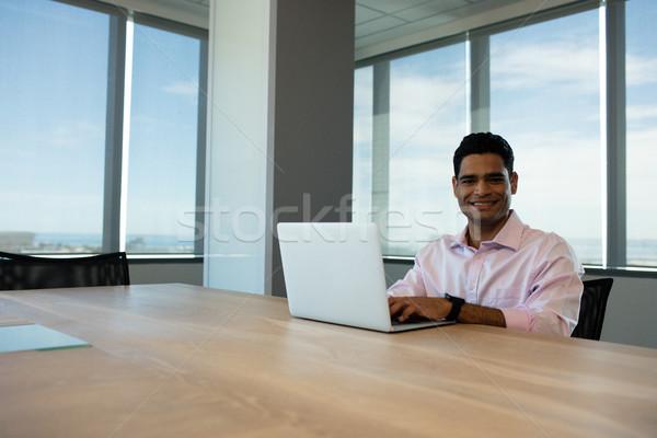 портрет улыбаясь бизнесмен используя ноутбук конференц-зал сидят Сток-фото © wavebreak_media