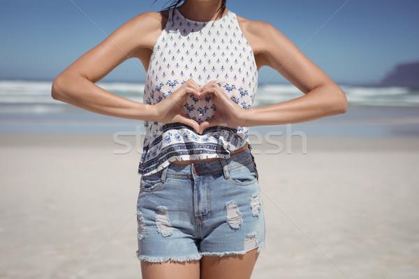 Középső rész nő készít szív alak kezek tengerpart Stock fotó © wavebreak_media