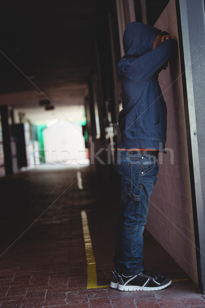 Side view of sad boy leaning on wall in corridor Stock photo © wavebreak_media