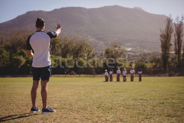 Coach instructing schoolgirls during sack race in park Stock photo © wavebreak_media