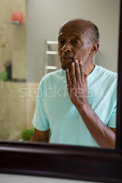 Mirror with reflection of concerned senior man touching his cheek Stock photo © wavebreak_media