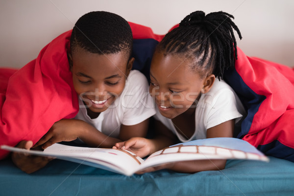 Smiling siblings reading book together while lying on bed Stock photo © wavebreak_media