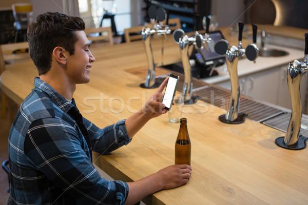Man with beer bottle using phone at bar Stock photo © wavebreak_media