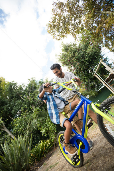 Tilt image of father assisting son for riding bicycle Stock photo © wavebreak_media