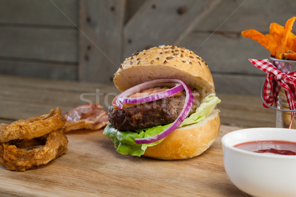 Stock photo: Hamburger, french fries, onion ring and tomato sauce on chopping board