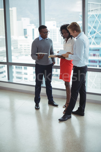Young business people discussing by glass windows Stock photo © wavebreak_media
