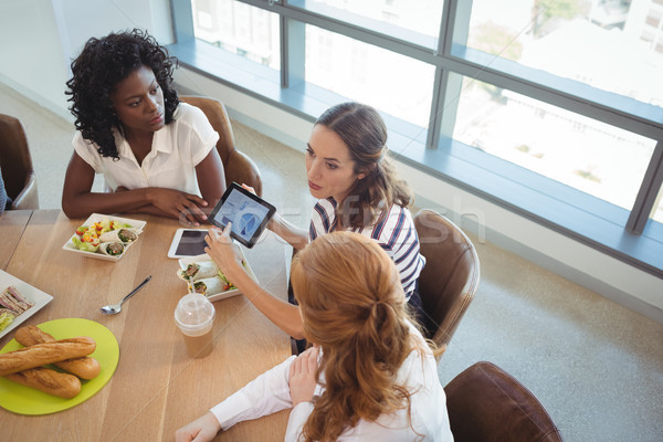 Female business colleagues discussing over digital tablet around breakfast table Stock photo © wavebreak_media