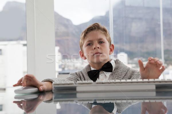 Serious businessman using keyboard at table Stock photo © wavebreak_media