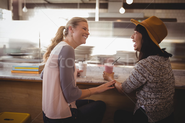 Cheerful female friends talking while sitting at coffee shop Stock photo © wavebreak_media