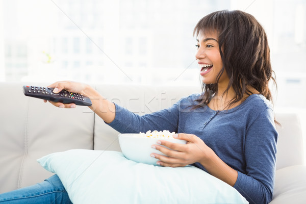 Smiling casual woman watching tv with popcorn Stock photo © wavebreak_media
