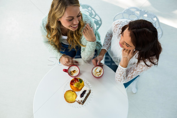 Kettő lányok ital kávé eszik sütemények Stock fotó © wavebreak_media