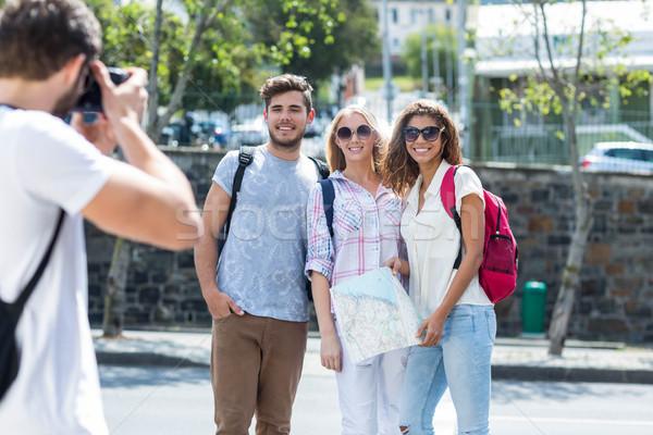 Hip man taking picture of his friends Stock photo © wavebreak_media