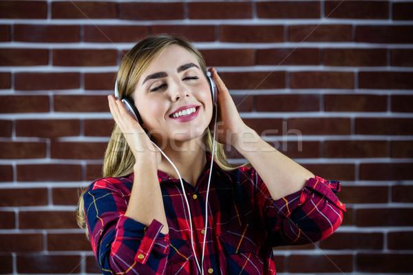 Joli femme blonde écouter de la musique mur de briques mur mode Photo stock © wavebreak_media
