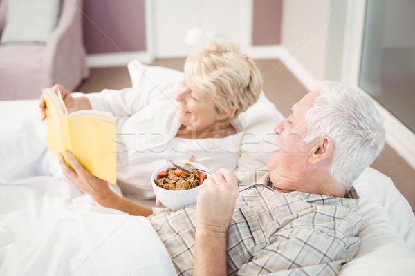 Couple reading book while having breakfast on bed Stock photo © wavebreak_media