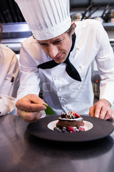 Male chef garnishing a dessert with a mint leaf on counter Stock photo © wavebreak_media