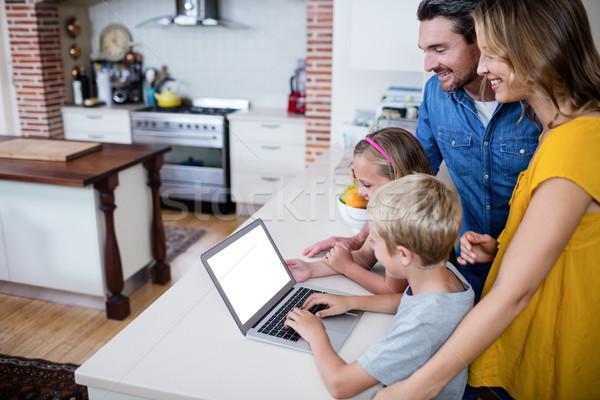 Parents and kids using laptop in kitchen Stock photo © wavebreak_media