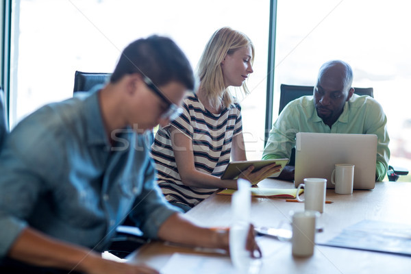 Colleagues interact at their desk using digital tablet and lapto Stock photo © wavebreak_media