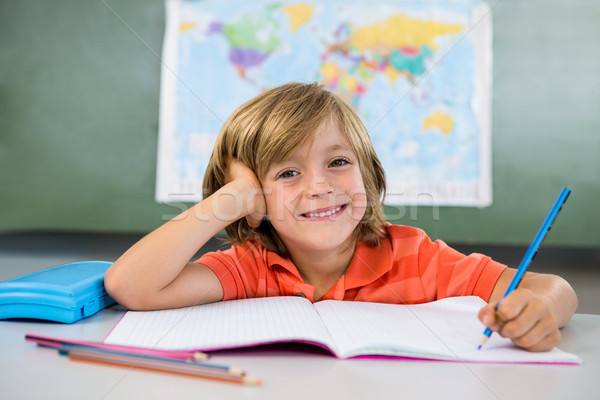 Smiling boy writing on book in classroom at school Stock photo © wavebreak_media