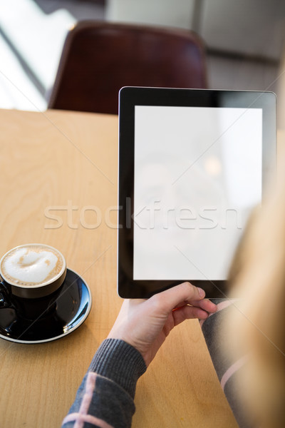Woman using digital tablet with cup of coffee on table Stock photo © wavebreak_media