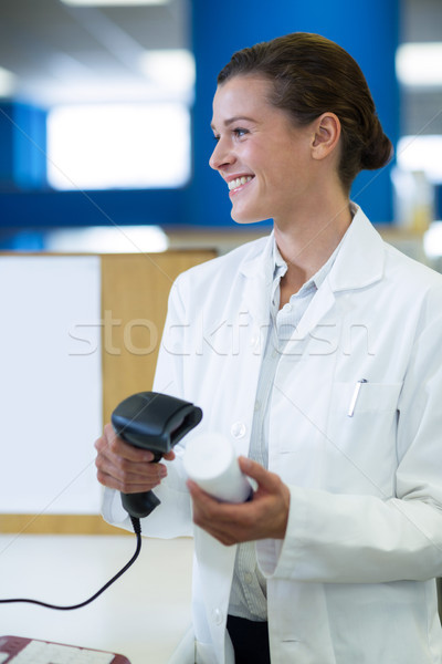 Smiling pharmacist using barcode scanner on medicine bottle Stock photo © wavebreak_media