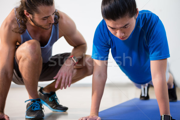 Fitness instructor helping fitness man with push-up Stock photo © wavebreak_media