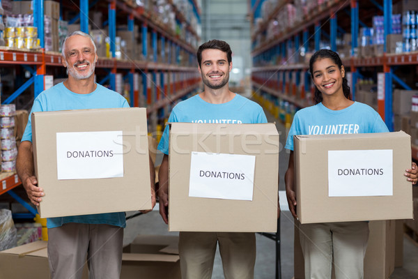 Portrait of three volunteers holding a donations box Stock photo © wavebreak_media