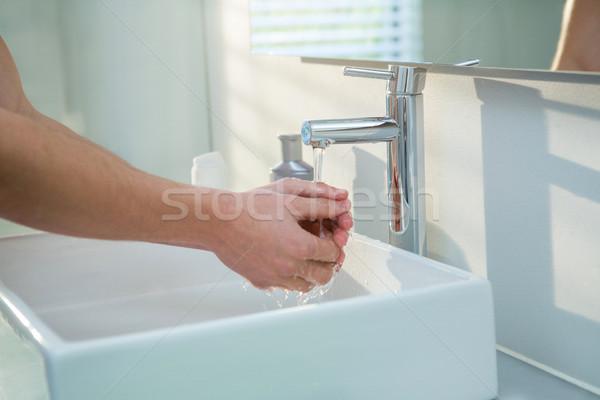 Man washing his hands in bathroom sink Stock photo © wavebreak_media