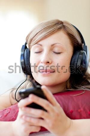 Attractive woman is listening the music with headphones  Stock photo © wavebreak_media