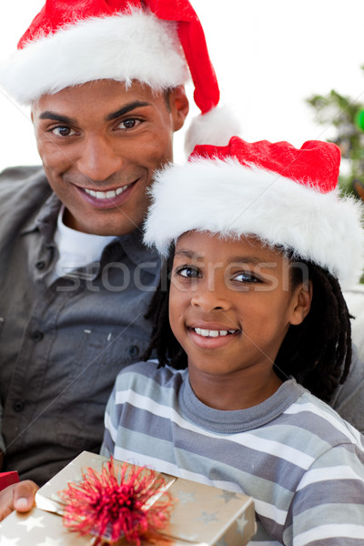 Portrait of a smiling Afro-American father and son holding a Christmas gift Stock photo © wavebreak_media