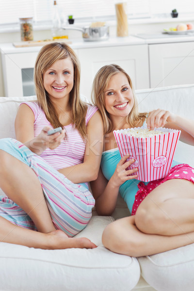 Two close female friends watching televison on the sofa eating popcorn in the living-room Stock photo © wavebreak_media