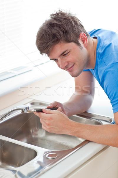 Assertive man repairing his sink in the kitchen at home Stock photo © wavebreak_media
