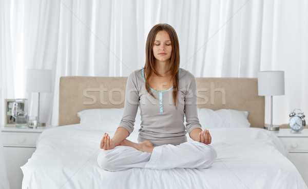 Young woman doing yoga exercises on the bed at home Stock photo © wavebreak_media