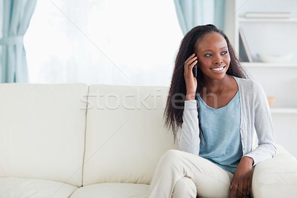Smiling woman phoning on sofa Stock photo © wavebreak_media