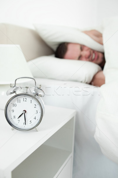 Portrait of a tired man covering his ears with a pillow while his alarm clock is ringing Stock photo © wavebreak_media