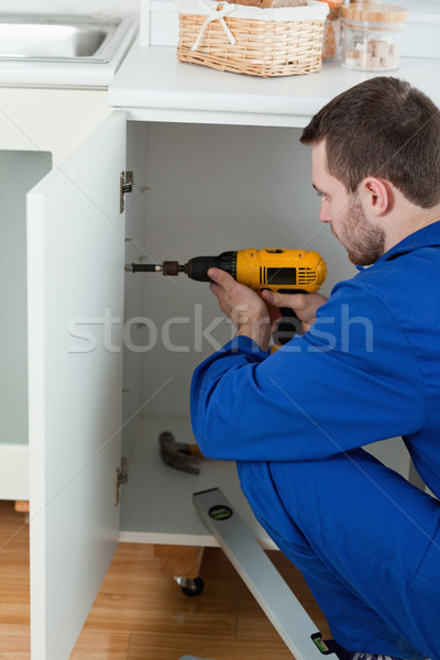 Portrait of a handyman fixing a door in a kitchen Stock photo © wavebreak_media