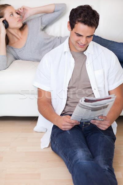Joven lectura noticias compañera escuchar música sofá Foto stock © wavebreak_media