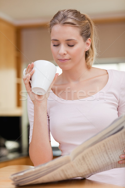 Stock photo: Portrait of a cute woman reading the news while having tea in her kitchen
