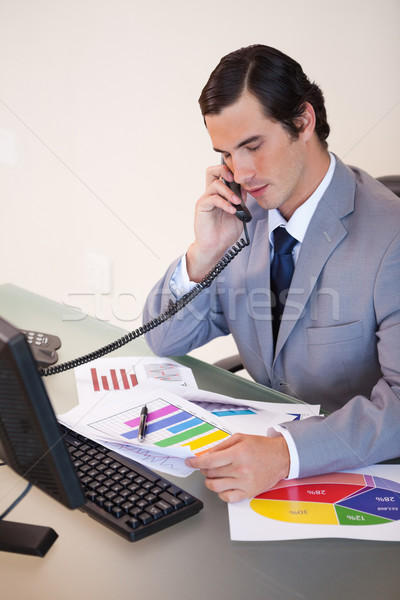 Stock photo: Young businessman on the phone talking about statistics
