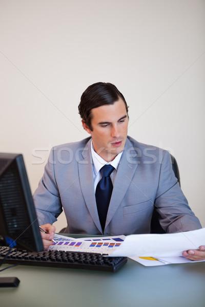 Stock photo: Young businessman doing paperwork