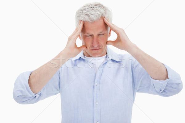 Tired man having a headache against a white background Stock photo © wavebreak_media